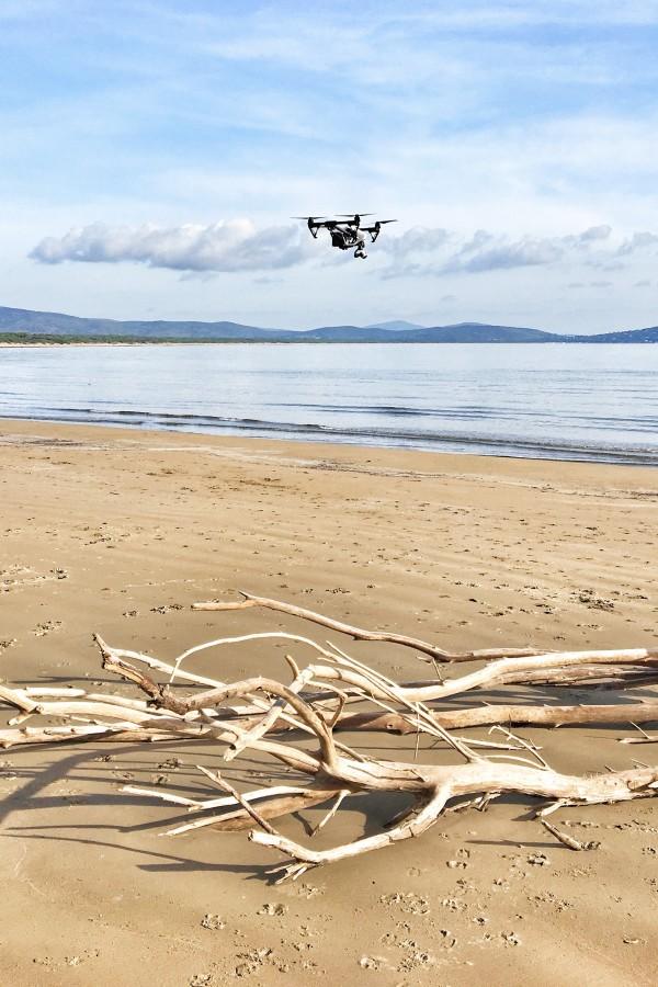 drone dji inspire 1 su spiaggia con tronco di albero e mare sullo sfondo